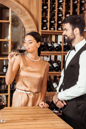 wine steward standing near woman while she tasting wine at wine store