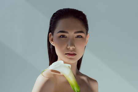 beautiful nude asian girl with calla flower, isolated on grey