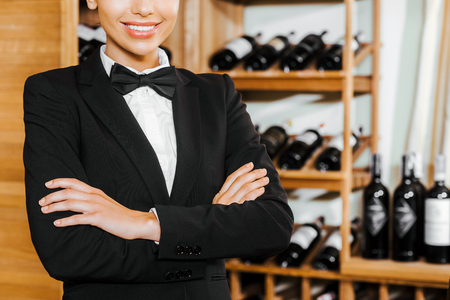 cropped shot of smiling female wine steward with crossed arms at wine store