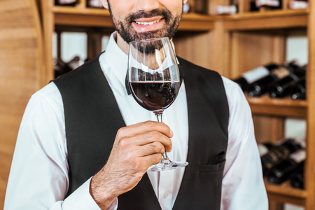 cropped shot of smiling sommelier sniffing red wine from glass at wine store Stock Photo