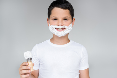 portrait of smiling preteen boy with brush in hand and shaving foam on face isolated on grey