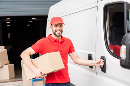 portrait of smiling delivery man in uniform with cardboard box standing near white van in street
