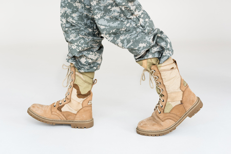 partial view of male soldier in camouflage clothing and boots on grey background Reklamní fotografie