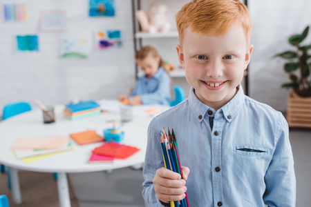 selective focus of happy red hair boy with pencils and classmate at table in classroom 写真素材 - 107661697