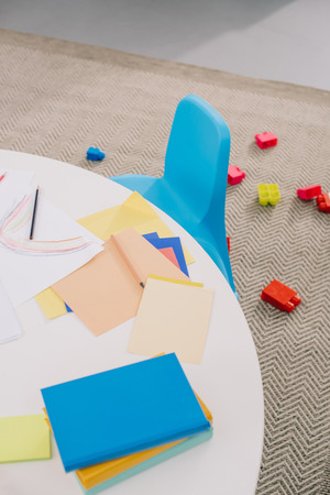close up view of empty papers for drawing on table and colorful bricks on floor in classroom