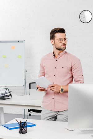 thoughtful young businessman leaning back at workplace at modern office
