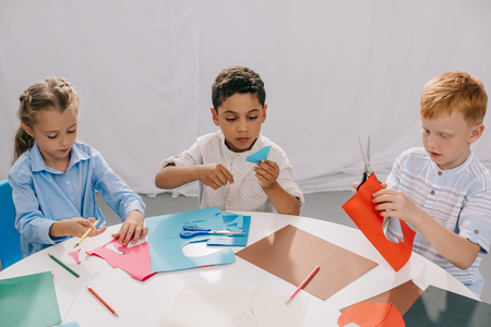 focused multiracial kids making paper applique in classroom
