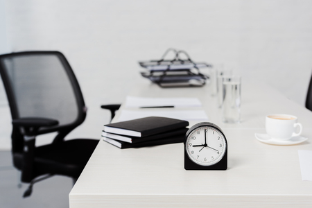 close-up shot of desk with stack of notebooks and alarm clock at modern office
