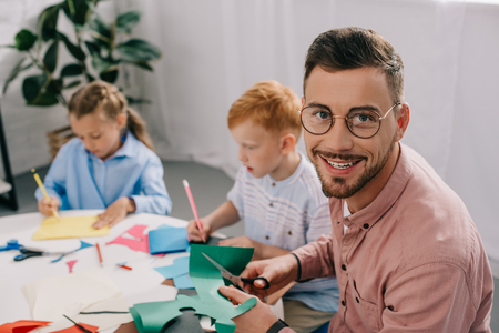 selective focus of smiling teacher and preschoolers making paper applique in classroom Stock Photo