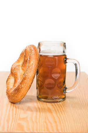 selective focus of beer with pretzel on wooden table on white background
