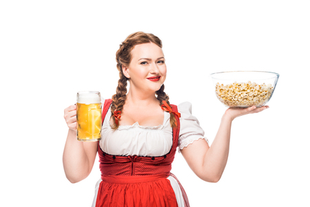 happy oktoberfest waitress in traditional bavarian dress holding bowl of popcorn and mug of light beer isolated on white background