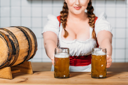 oktoberfest waitress in traditional bavarian dress putting mugs of light beer on bar counter with beer barrel 写真素材