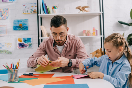 portrait of teacher and cute preschooler cutting papers with scissors att able in classroom Stock Photo