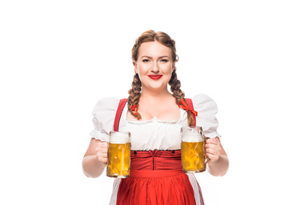 smiling oktoberfest waitress in traditional german dress with two mugs of light beer isolated on white background Reklamní fotografie
