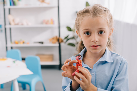 portrait of little kid with plasticine in hands looking at camera in classroom