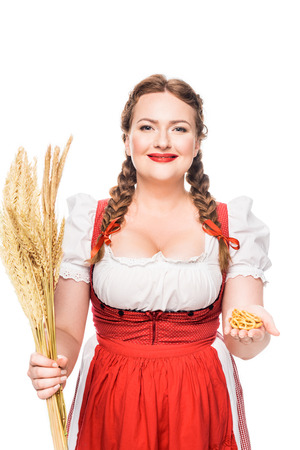 oktoberfest waitress in traditional bavarian dress showing little pretzels and holding wheat ears isolated on white background