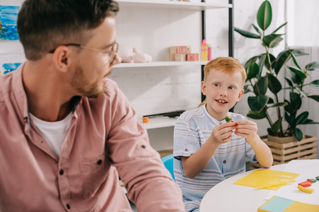 teacher and red hair preschooler with plasticine sculpturing figures at table in classroom