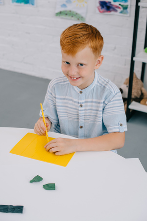 high angle view of smiling red hair boy sitting at table with colorful plasticine for sculpturing in room
