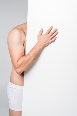 cropped shot of man with blank banner in underwear isolated on grey Stock Photo