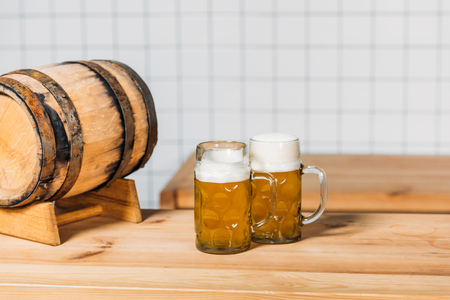 selective focus of mugs with light beer and barrel at bar counter Stock Photo