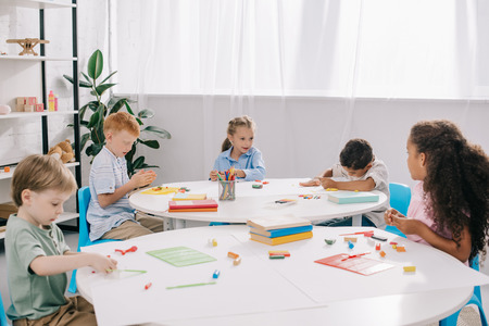 cute multiethnic preschoolers sculpturing figures with plasticine at tables in classroom