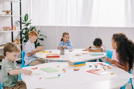 cute multiethnic preschoolers sculpturing figures with plasticine at tables in classroom