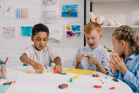 portrait of cute multiethnic preschoolers sculpturing figures with plasticine in classroom Reklamní fotografie