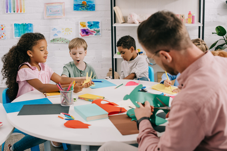 teacher and multiracial preschoolers with colorful papers and scissors making paper applique in classroom