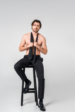 shirtless man in black pants with tie siting on chair on grey background Stock Photo