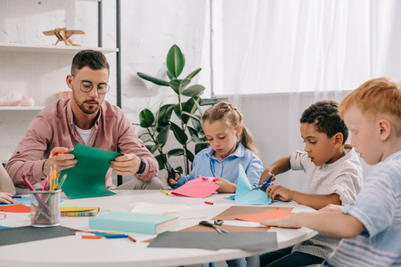 teacher and multiracial preschoolers cutting colorful papers with scissors in classroom Stock Photo
