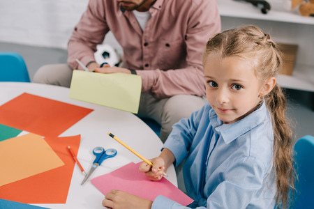 teacher and cute preschooler cutting papers with scissors att able in classroom