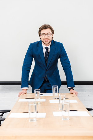 smiling young businessman looking at camera while leaning on table at conference hall and looking at camera Stock Photo