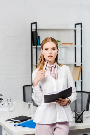attractive young businesswoman with notebook leaning back at workplace at modern office Stock Photo