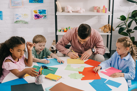 multiethnic preschoolers and teacher making paper applique at table in classroom
