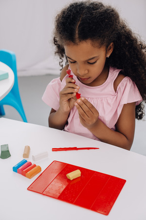 african american kid with plasticine in hands sculpturing figure at table Imagens
