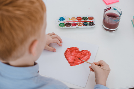 partial view of preschooler red hair boy drawing heart on paper at table in classroom