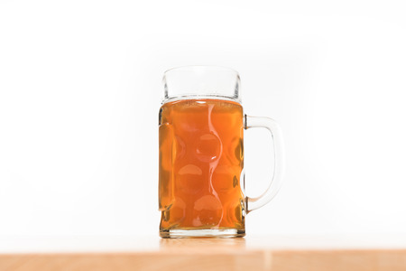 close up view of beer in mug on wooden table on white background Stock Photo