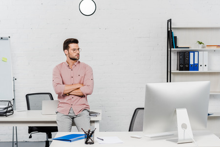 handsome young businessman leaning back at workplace at modern office Stock Photo