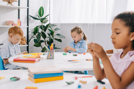selective focus of multiracial kids with plasticine at tables in classroom