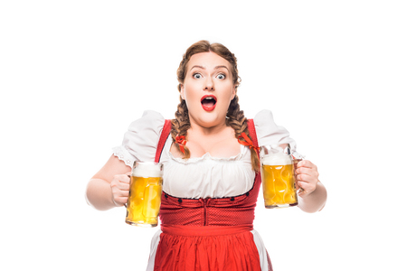 shocked oktoberfest waitress in traditional bavarian dress with mugs of light beer isolated on white background