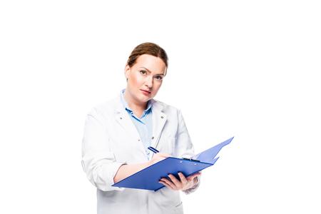 ernsthafte Ärztin im weißen Kittel, die in Zwischenablage geschrieben auf lokalem Hintergrund schreibt