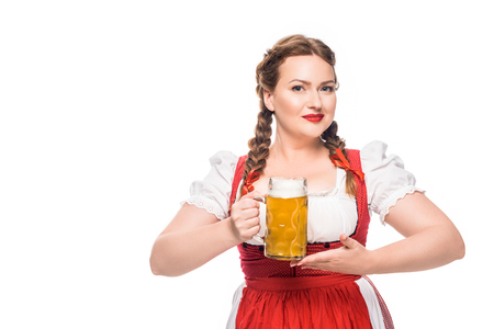 attractive oktoberfest waitress in traditional bavarian dress holding mug of light beer isolated on white background