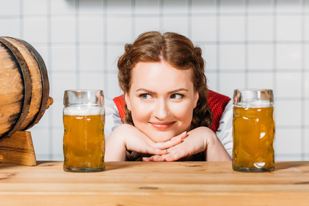 smiling oktoberfest waitress in traditional bavarian dress sitting between two mugs of light beer on bar counter