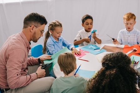 partial view of male teacher and multiracial preschoolers cutting colorful papers with scissors at table in classroom 写真素材 - 107670318