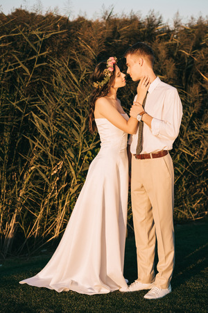 beautiful happy young tender wedding couple able to kiss on green grass