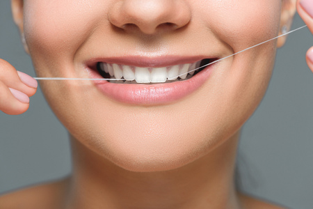 partial view of smiling woman with beautiful white teeth and dental floss isolated on grey Reklamní fotografie