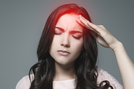 sick woman suffering from headache, with red painful point, isolated on grey