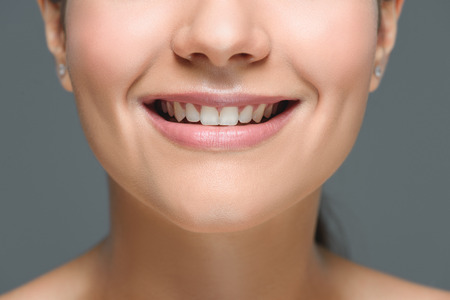 partial view of smiling woman with beautiful white teeth isolated on grey 스톡 콘텐츠