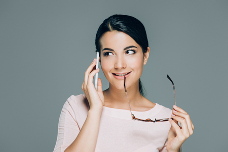 portrait o beautiful brunette woman with eyeglasses talking on smartphone isolated on grey Imagens