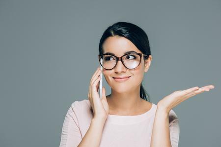 portrait o beautiful brunette woman in eyeglasses talking on smartphone isolated on grey